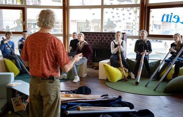 Leerlingen van de Kleine Kapitein in Bakel proberen geluid te krijgen uit didgeridoos.