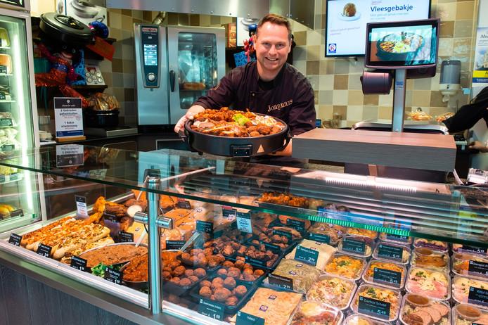 Slager Jean-Pierre Jongmans uit Klundert toont een hapjespan. In de vitrine de kant en klaar maaltijden die gretig aftrek nemen.