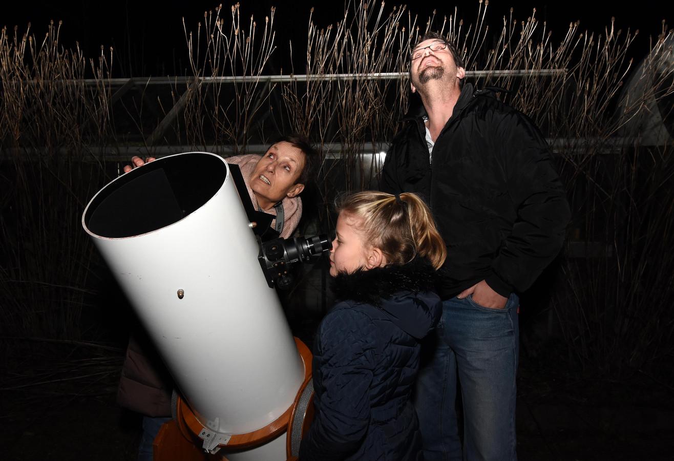 Ans Viervant en Ruben en Sirina Hoogendoorn bij de telescoop.