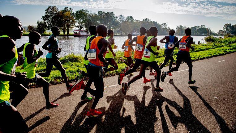 De kopgroep in de marathon van 2014 loopt langs de Amstel. Koen Raymaekers: 'Als je daar op de terugweg wind tegen hebt, komt de wind over het water en dat is heel naar.' Beeld Jerry Lampen/ANP