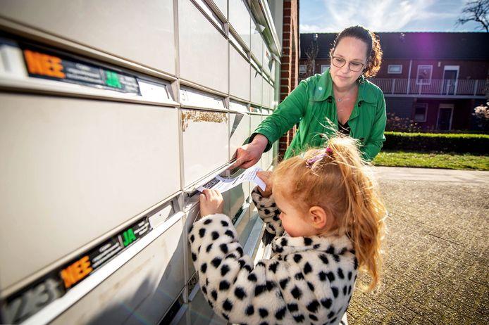 De 4-jarige Lisa verspreidt samen met haar moeder Sylvia Walraven flyers van Corona Hulp Wijchen.