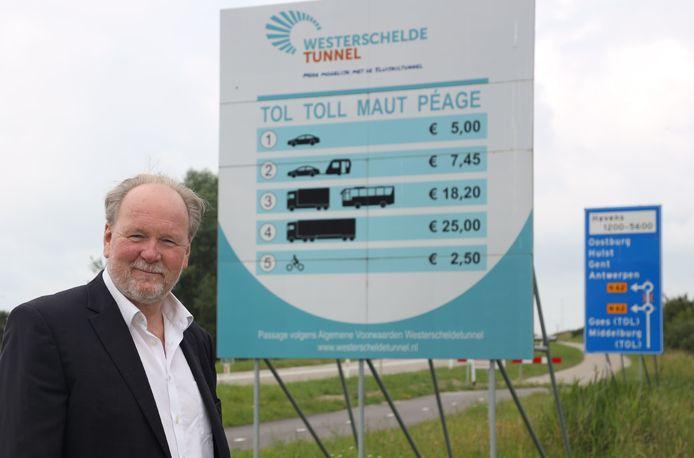 Voorzitter Cees Liefting van Zeeland Tolvrij bij een tariefbord voor de Westerscheldetunnel.