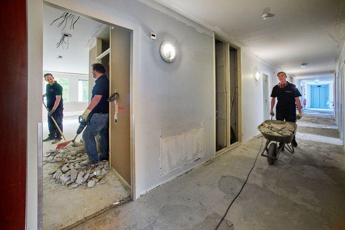 Keukenmanagers Theo en Arnoud slopen een muurtje, bedieningsmedewerker Coen voert puin af in Hotel de Naaldhof in Oss.