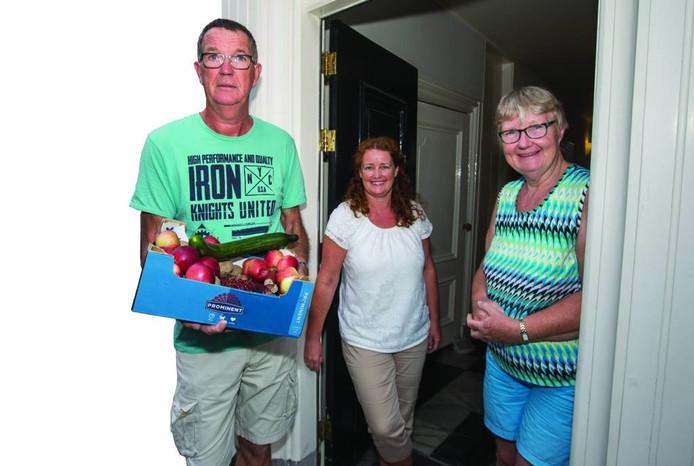 Elise Versteeg (midden) heeft zojuist de doos met groente en fruit aan Liesbet en Wim Verschoor uit Oud-Vossemeer gegeven. foto Johan van der heijden