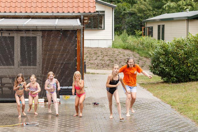 Joy Grisel van het animatieteam rent samen met kinderen langs een spetterende sproeier op familiecamping De Vossenburcht in IJhorst.