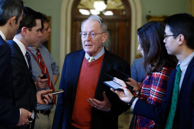 De Republikeinse senator Lamar Alexander uit Tennessee praat met verslaggevers als hij vrijdag op weg is naar de vergaderzaal van de Senaat waar het impeachmentproces tegen president Trump wordt gehouden.  Beeld AP
