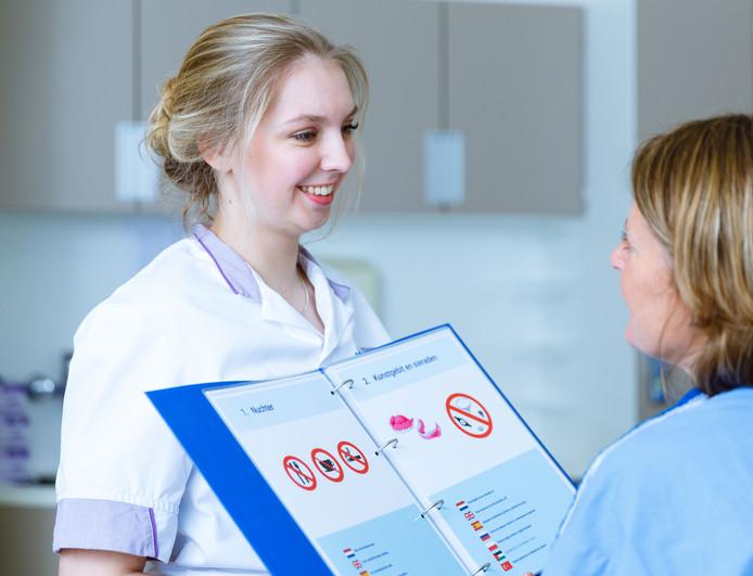 Michelle van Gerven toont een patiënte de bladen die horen bij nuchter blijven voor een onderzoek en wat te doen met kunstgebit en sieraden tijdens een ingreep. Foto MMC/Bram Saeys