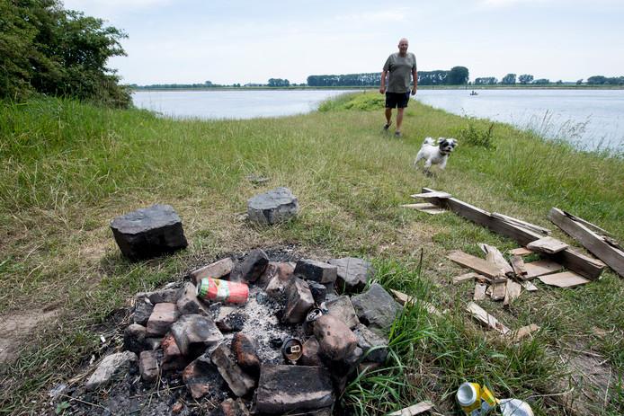 Ton Veltman loopt met zijn hondje langs de resten van een barbecue op een van de Waalstrandjes.