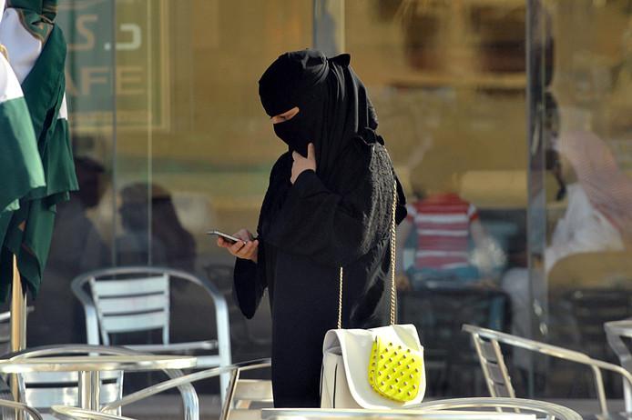 Een Saudische vrouw kijkt op haar telefoon.