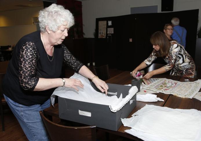 Mia Marse (links) zorgt voor het vervoer van de oude borduurwerken uit het museum de Vier Ambachten.