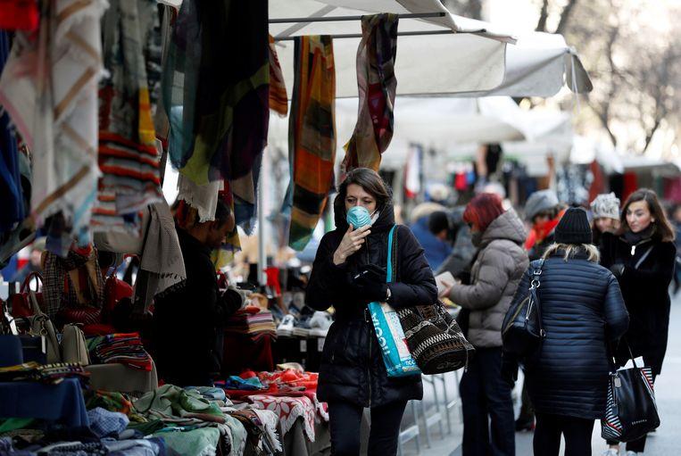 Een vrouw draagt een gezichtsmasker op de markt in Milaan.  Beeld REUTERS