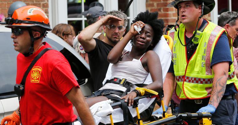 Reddingsmedewerkers helpen een gewonde vrouw die in aanraking kwam met een groep demonstranten. Beeld AP
