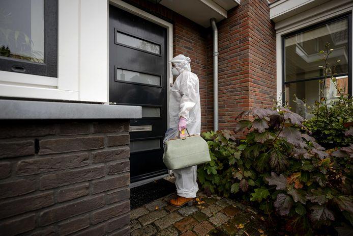 Een huisarts in beschermende kleding arriveert bij een patient thuis.