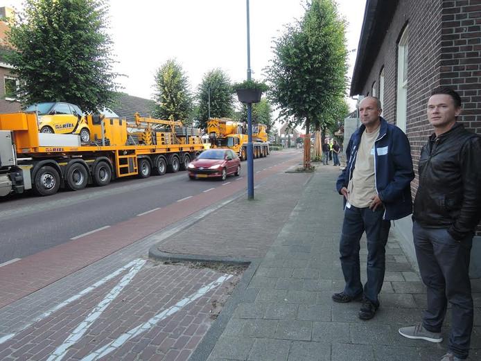 Hennie van Alphen (l) en Joris van Gemert van opdrachtgever Peelrand Wonen kijken naar de bouwkraan en overleggen over de afzettingen.