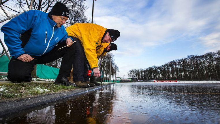 De ijsmeesters (vlnr) Hilko Odink, Dirk Jan van Faassen en Erik Hekman van ijsvereniging Ons Genoegen in het Overijsselse Gramsbergen meten de ijsdikte na ruim 24 uur vorst. Beeld anp