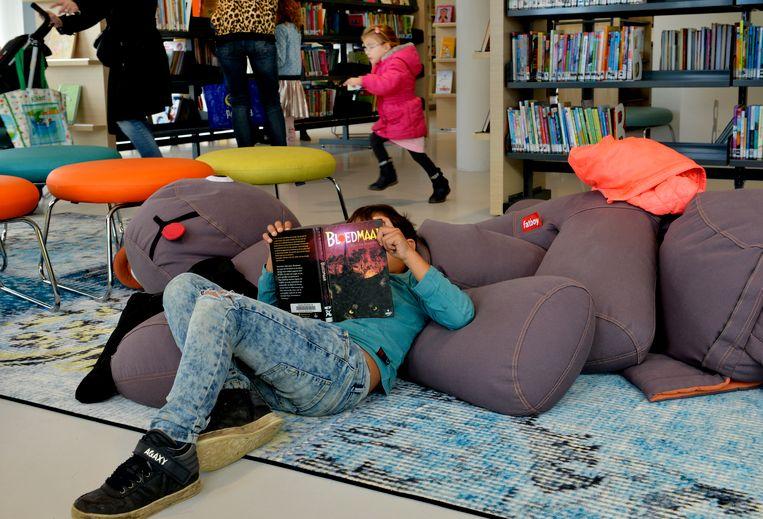 Een meisje leest een boek in de openbare bibliotheek in Tiel. Beeld Hollandse Hoogte / William Hoogteyling