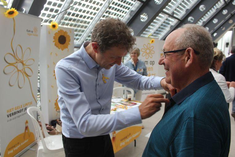 Frank Deboosere speldt een geel lintje op bij een bezoeker van het ziekenhuis.