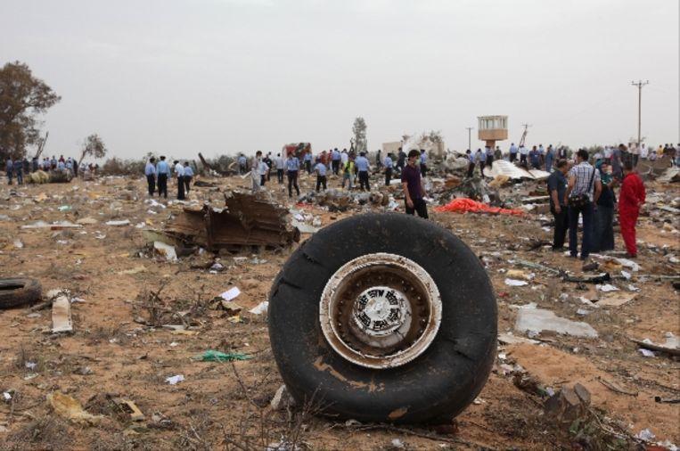 Reddingswerkers lopen tussen de wrakstukken van het Libische vliegtuig. (AFP) Beeld AFP