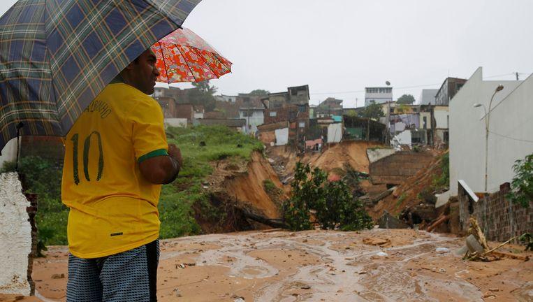 Een voetbalfan kijkt vandaag naar huizen in Natal die zijn weggevaagd door de regen. Beeld reuters