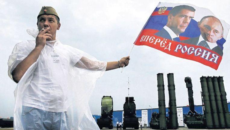 Een man zwaait met een vlag met de beeltenissen van premier Medvedev en president Poetin, bij een militaire show, nabij Moskou. Beeld epa
