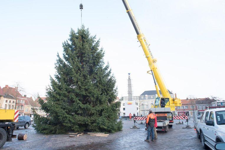 De reusachtige kerstboom wordt vakkundig op de markt geplaatst.