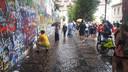 Graffiti spuitende toeristen bij de Lennon wall