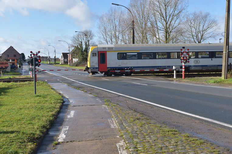 Treinen passeren stapvoets aan de overweg.