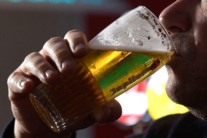 Een man drinkt Jupiler.