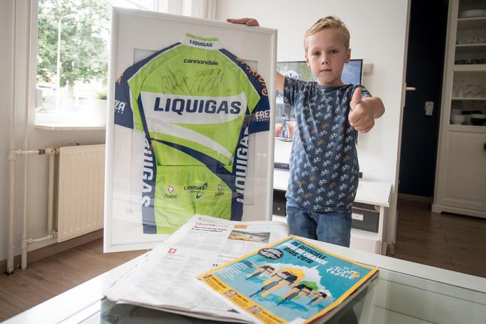 Mees met zijn door Sagan en Nibali gesigneerde shirt. Op de achtergrond is de tv afgestemd op de Tour de France. Foto: Lenneke Lingmont