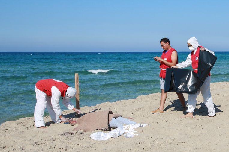 Medewerkers van het Rode Kruis staan bij het lichaam van een verdronken migrant in Al Khoms, Libië.  Beeld AP