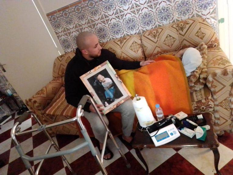 Brahim Aoulad Lfadil zorgt nu in een gehuurd apartementje in Tanger voor zijn moeder, die in maart twee herseninfarcten kreeg. Hij houdt een foto vast van zijn 2-jarige zoontje. Beeld Brahim Aoulad Lfadil