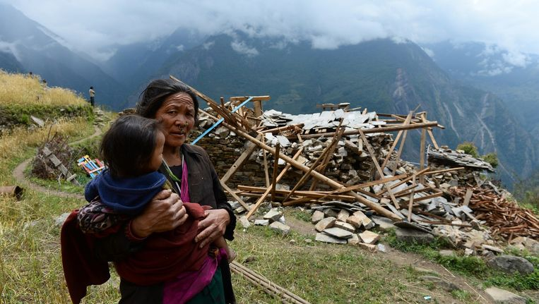 Een moeder draagt haar zoon terwijl ze langs een verwoest huis loopt in het dorp Uiya, in het Gorkha-district. Beeld afp