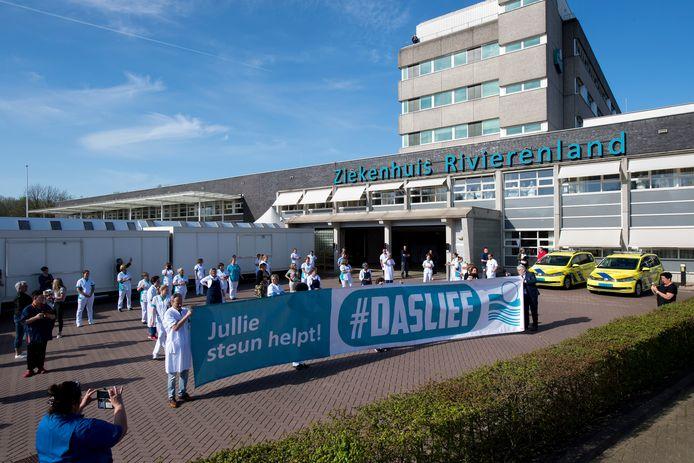 Hulpdiensten zoals politie en brandweer steken verzorgend personeel van ziekenhuis Rivierenland een hart onder de riem vanwege strijd tegen coronavirus en het personeel waardeert dat met een tegenspandoek.