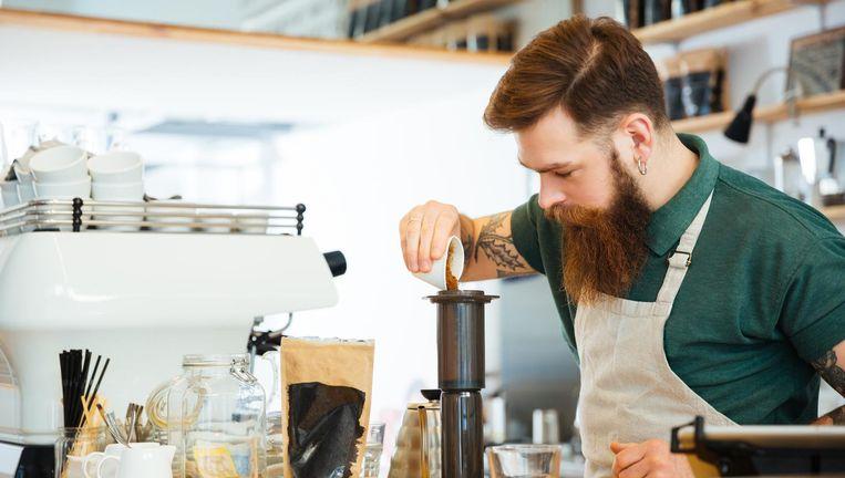 Barista maakt koffie in een koffieshop. Beeld Colourbox