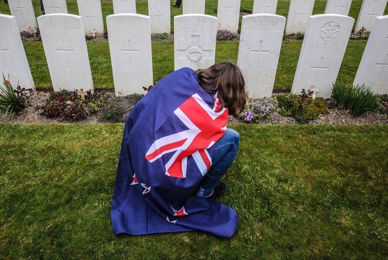 Een bezoekster knielt bij één van de grafstenen.