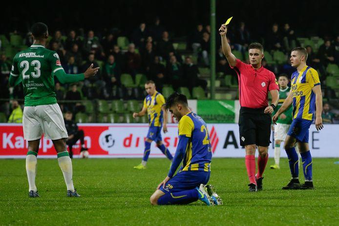 Scheidsrechter Edgar Bijl geeft Dordrecht-verdediger Noah Lewis zijn tweede gele kaart.