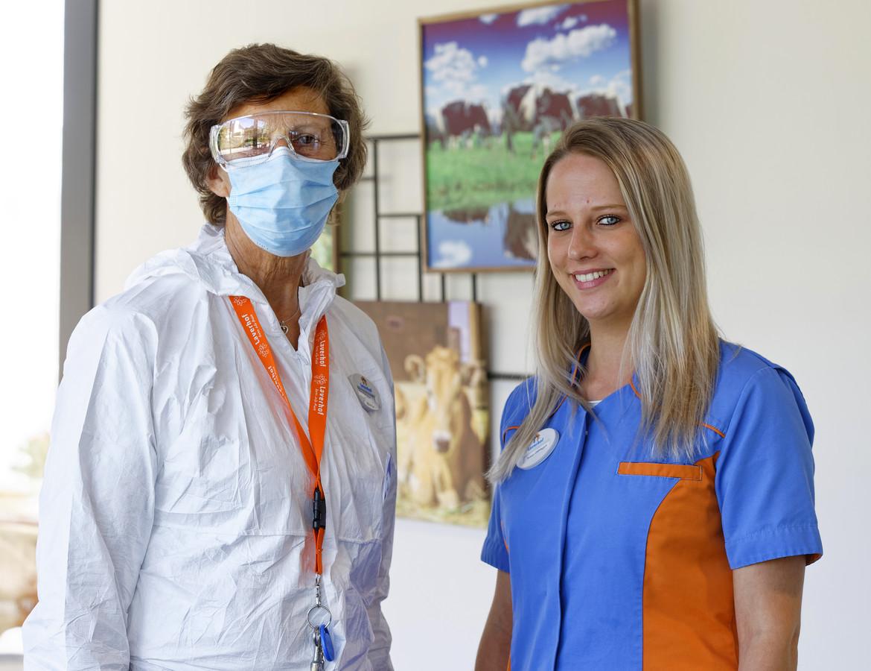Susan Olijslagers, rechts, in normale kleding. Als er corona heerst op een afdeling dan dragen medewerkers witte pakken, een mondkapje en spatbril. Een mondkapje dragen ze standaard in het verpleegtehuis.