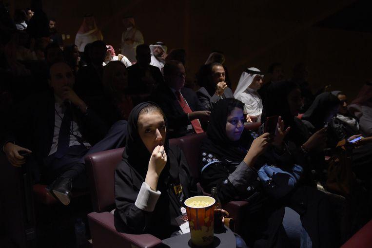 Een vrouw eet popcorn in een bioscoop in Riyadh. Vorig jaar trok de regering het verbod op bioscopen in. Vrouwen en mannen zitten er apart van elkaar, maar wel in één zaal. Beeld AFP