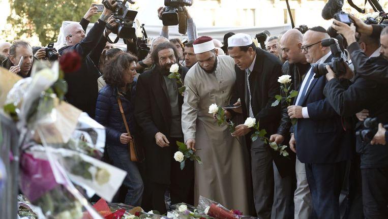 De Franse auteur Marek Halter (4e van links), Imam van de Drancy Moskee, Hassene Chalghoumi (6e van links), en overige leden van joodse en moslim gemeenschappen leggen een bloem bij een gemaakt herdenkingsmonument nabij de Bataclan concertzaal. Beeld afp