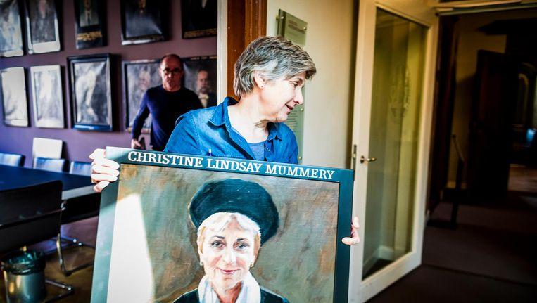 Corrie van Maris tijdens het vervangen van de oude portretten en het ophangen van de nieuwe vrouwenportretten in de Senaatskamer in de Universiteit Leiden Beeld Freek van den Bergh / de Volkskrant