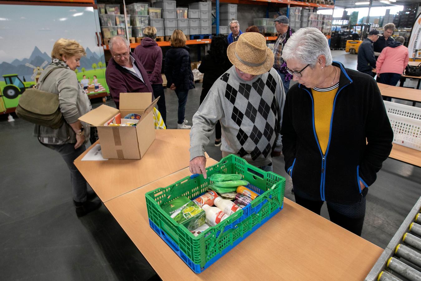 Klanten bekijken in een Eindhovense voedselbank het aanbod. Foto Kees Martens