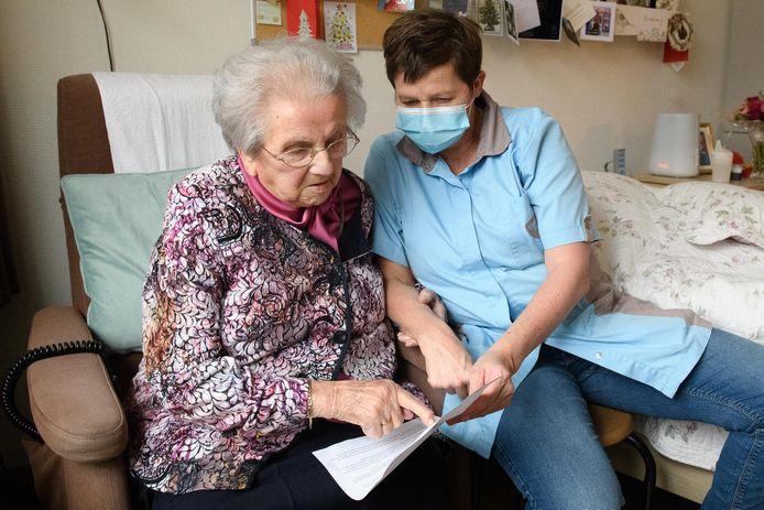 Medewerker Alien Smelt van verpleeghuis De Schutse in Rijssen neemt met Aaltje Scheepers (94) de uitnodiging tot vervroegde vaccinatie door. Mevrouw Scheepers ervaart de coronatijd als 'heel moeilijk'.