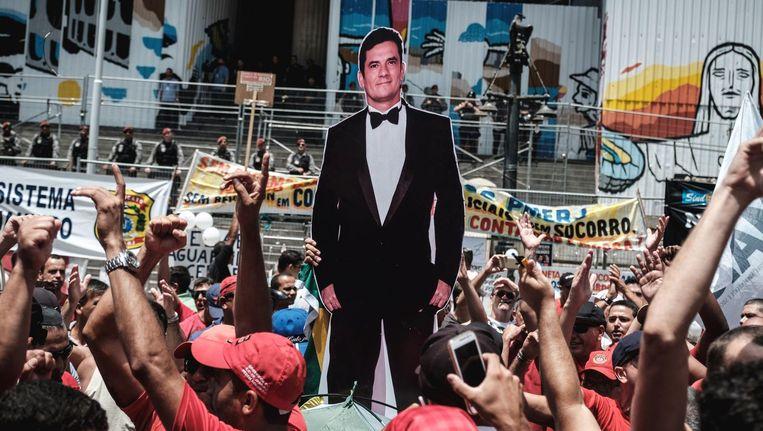 Demonstranten met een kartonnen afbeelding van Sergio Moro. Beeld null