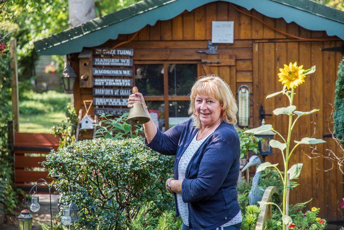 Juf Ellie in haar achtertuin met de oude schoolbel van het Koningshofke