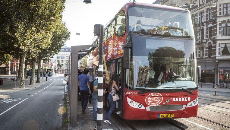 Naast de busdienst heeft Amsterdam als enige stad ter wereld ook een hop-on-hop-off-boot. Beeld Floris Lok