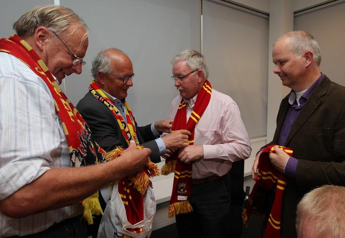 Harry Brink (links) ging ver in zijn liefde voor Go Ahead Eagles. Zo was hij lid van een actiegroep die in 2014 de hele gemeente Olst-Wijhe roodgeel wilde kleuren. Hier deelt hij samen met Bernhard ten Have sjaaltjes in de clubkleuren uit aan de beoogde wethouders Anton Bosch en Marcel Blind (rechts).