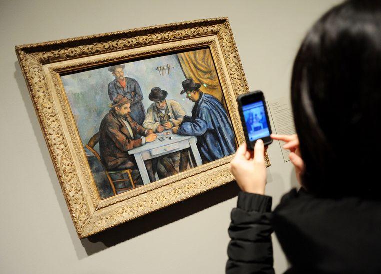 Een vrouw maakt een foto van Paul Cézanne's De kaartspelers Beeld afp