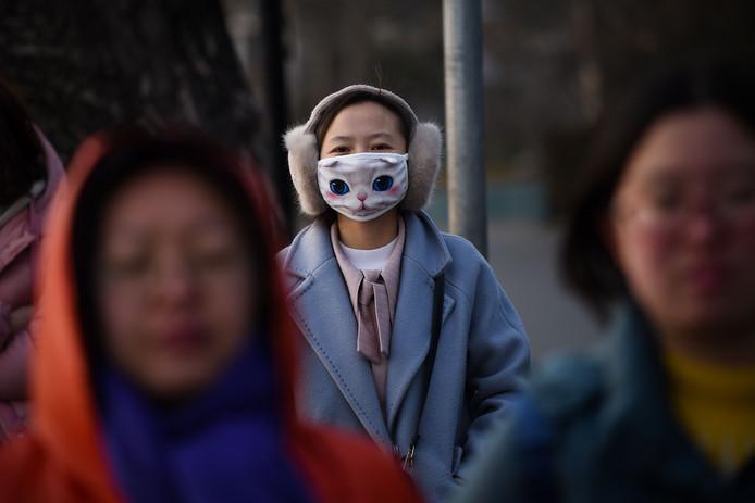Een jonge Chinese vrouw draagt een mondkapje met kattenogen terwijl ze langs een drukke weg loopt in Beijing. Foto Wang Zhao