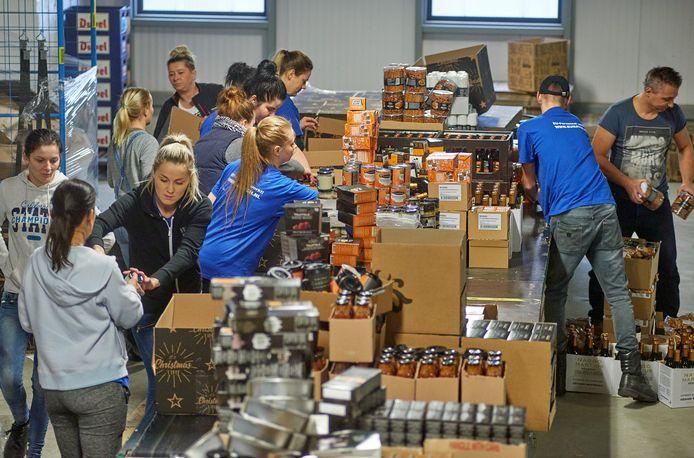 Het vullen van kerstpaketten bij Sligro in een gehuurd distributiecentrum van Goossens in Veghel.