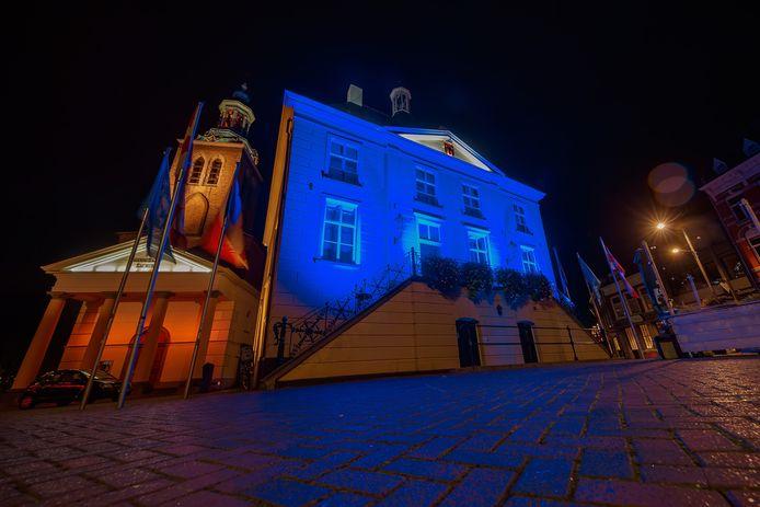 Het oude raadhuis is blauw verlicht naast de lege, opgestapelde terrassen.
